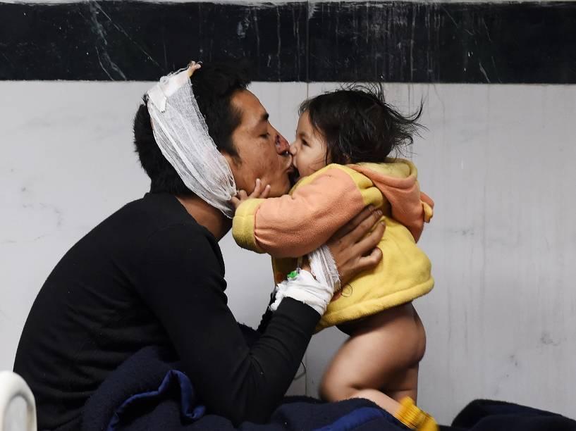 Homem ferido brinca com sua filha em um hospital de Katmandu, Nepal - 26/04/2015