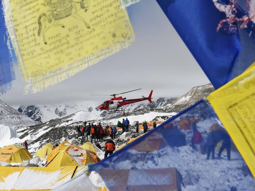 Bandeiras com orações são vistas enquanto um helicóptero resgata as vítimas da avalance no acampamento-base do Monte Everest - 26/04/2015