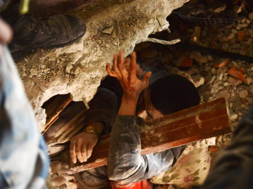 Equipe de resgate tenta retirar um sobrevivente debaixo dos escombros de uma casa um dia depois do terremoto em Katmandu, Nepal - 26/04/2015