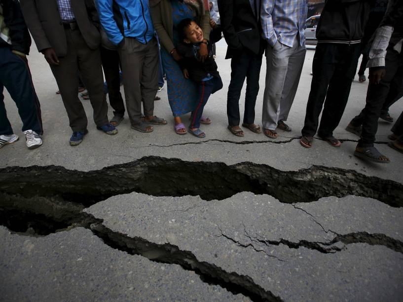 Pessoas se reúnem perto das rachaduras em uma estrada causadas pelo terremoto em Bhaktapur, Nepal - 26/04/2015
