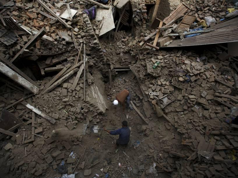Pessoas buscam por familiares entre os escombros das casas que desabaram com o terremoto em Bhaktapur, Nepal - 26/04/2015