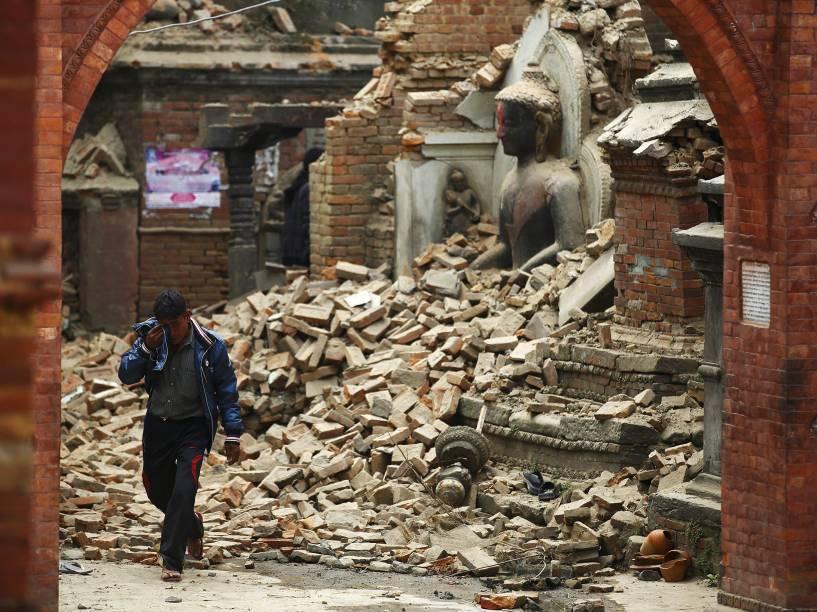 Homem chora enquanto caminha próximo a uma estátua de Buda em um santuário danificado pelo terremoto em Bhaktapur, Nepal - 26/04/2015