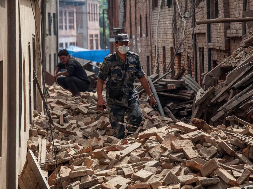 Policiais caminha em uma rua coberta de escombros em Bhaktapur, Nepal - 26/04/2015