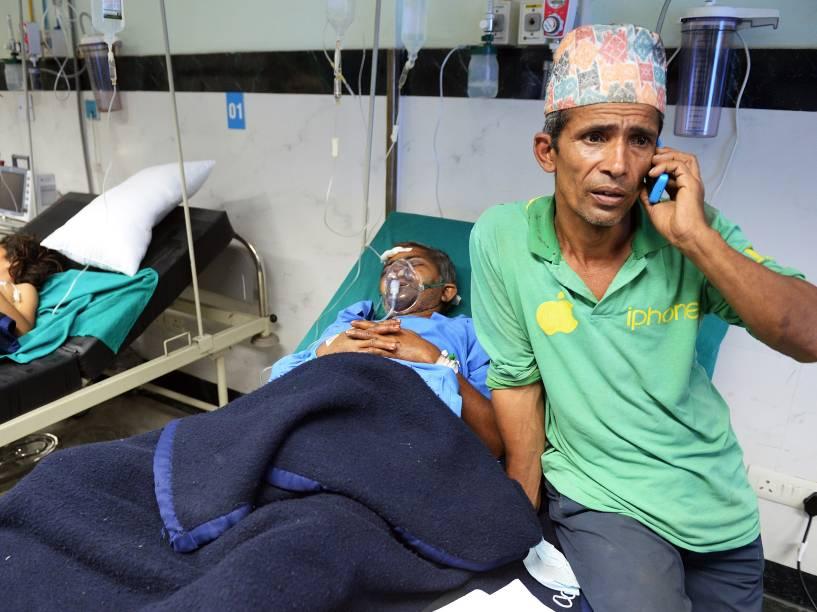 Homem fala ao telefone enquanto seu familiar recebe atendimento em um hospital de Katmandu - 26/04/2015