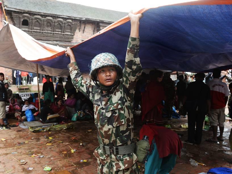 Integrante das forças de segurança do Nepal monta uma tenda para atender feridos em Bhaktapur - 26/04/2015