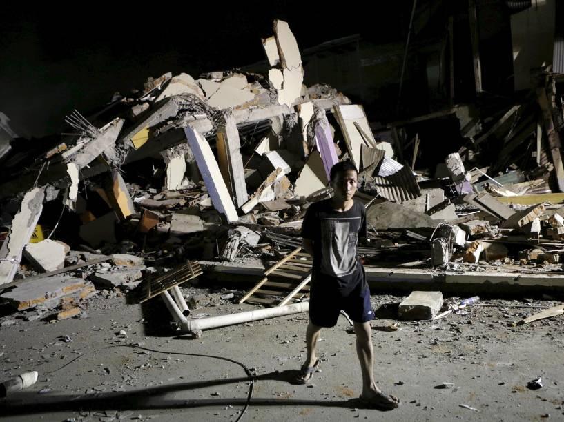 Menino caminha próximo a um hotel que desabou após o terremoto que atingiu a costa do Pacífico, em Portoviejo, no Equador - 17/04/2016