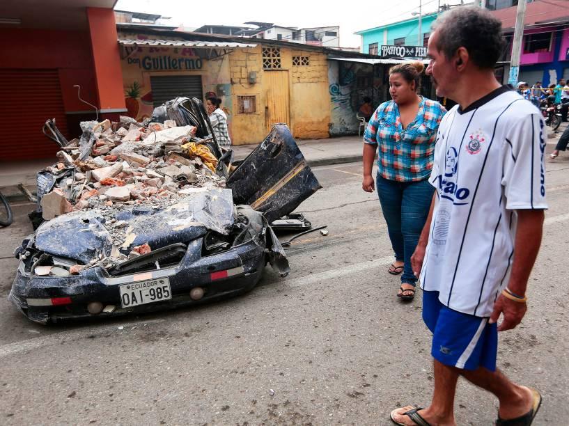 Moradores da cidade de Portoviejo, no Equador, caminham próximo a um carro, destruído após forte terremoto atingir o país. Ao menos 230 pessoas morreram - 17/04/2016