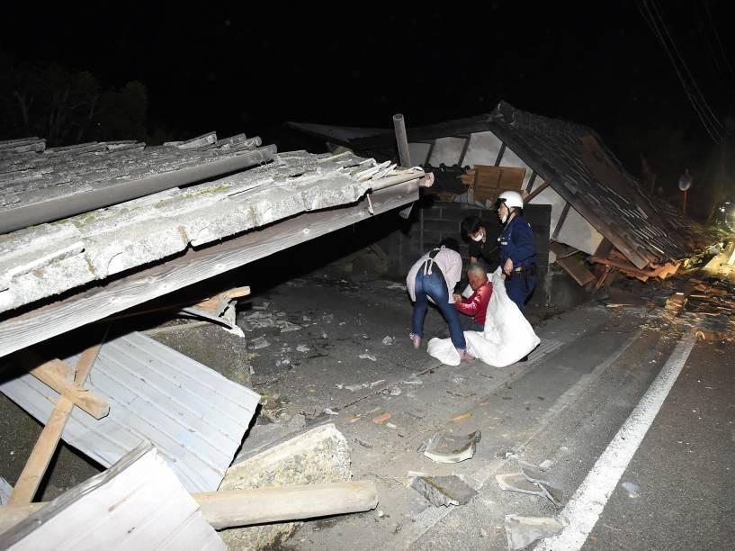 Moradores são retirados de suas casas por equipes de resgate após terremoto atingir a cidade de Kumamoto, sudoeste do Japão - 14/04/2016
