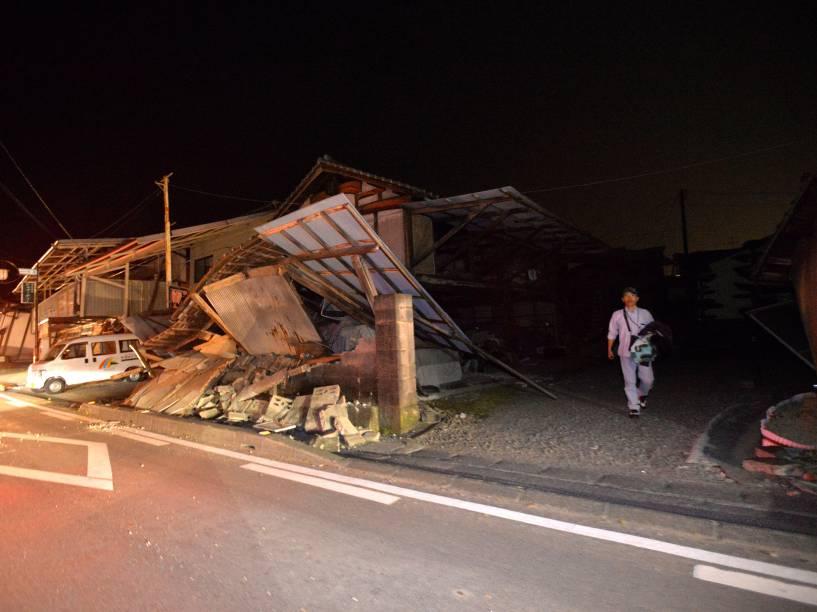Homem caminha próximo a uma casa destruída após forte tremor que atingiu a cidade de Kumamoto, sudoeste do Japão - 14/04/2016