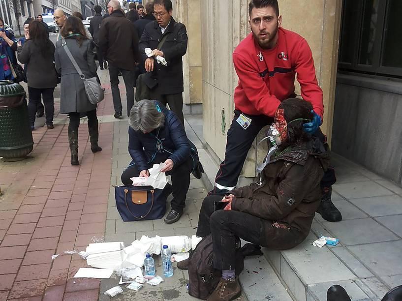 Homem ajuda uma mulher ferida do lado de fora da estação de metrô Maelbeek em Bruxelas, após ataque terrorista no local - 22/03/2016