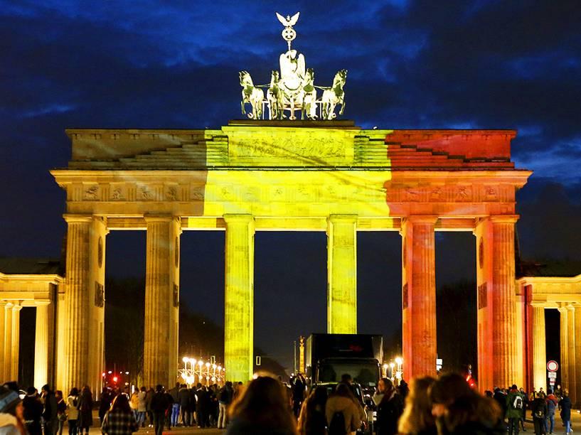 Belgas em frente ao Portão de Brandemburgo, iluminado com as cores da bandeira do país (vermelho, amarelo e preto), em tribuno às vítimas dos atentados em Bruxelas, nesta terça-feira (22). O grupo Estado Islâmico assumiu a autoria dos ataques