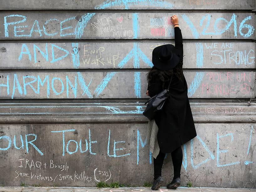 Mulher escreve mensagens de apoio, em parede da Bolsa de Valores de Bruxelas, aos familiares que perderam seus parentes nos atentados, nesta quarta-feira (23)