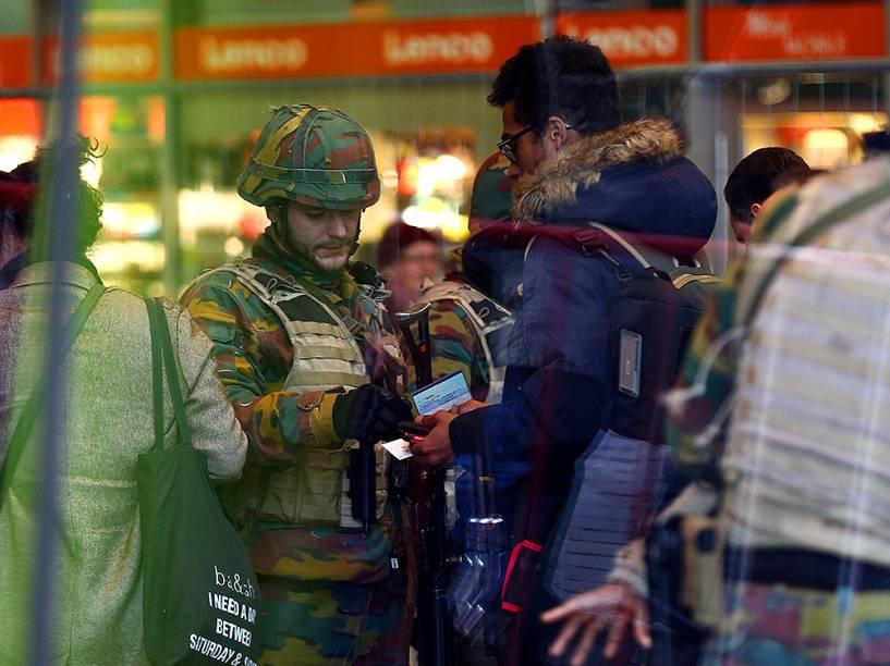 Soldado checa identificação de homem, em estação de trem de Bruxelas, na Bélgica, nesta quarta-feira (23), um dia depois dos atentados comandados pelo Estado Islâmico, deixarem dezenas de mortos