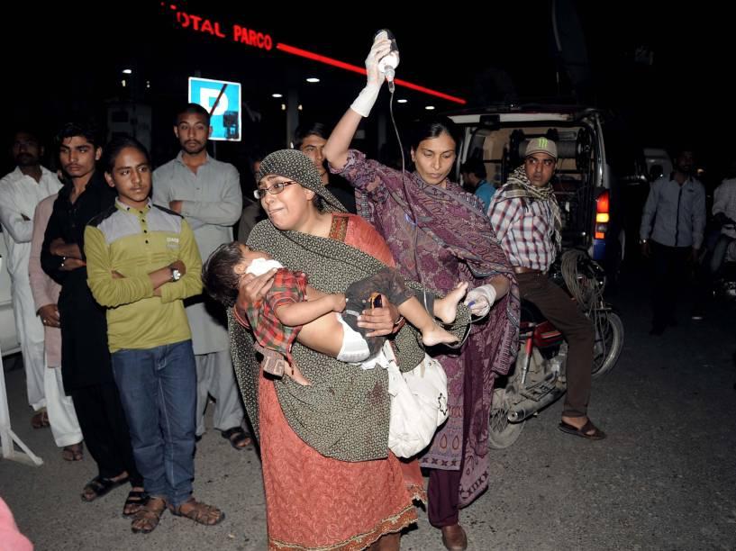 Mulher carrega uma criança ferida para o hospital, após atentado a bomba em Lahore, no Paquistão - 27/03/2016