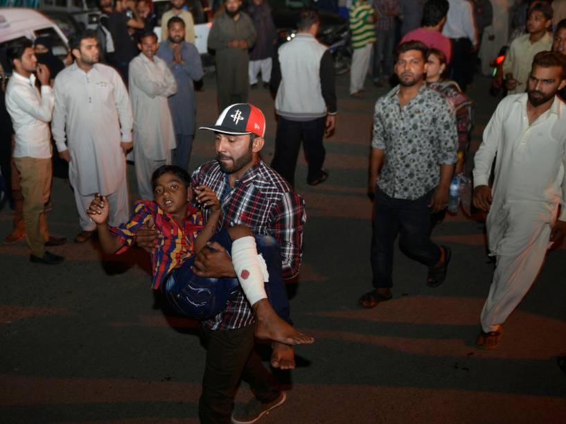 Homem carrega uma criança ferida para o hospital, após atentado a bomba em Lahore, no Paquistão - 27/03/2016<br><br>