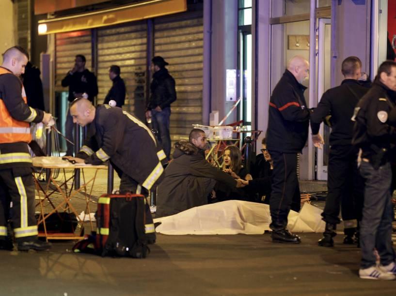 Serviços de resgate trabalham perto dos corpos cobertos fora de um restaurante na sequência de um tiroteio em Paris, França - 13/11/2015