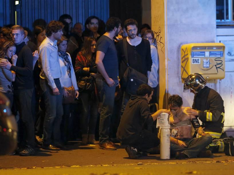 Bombeiro ajuda um homem ferido nos arredores da sala de concertos Bataclan na sequência de um tiroteio em Paris, França - 13/11/2015
