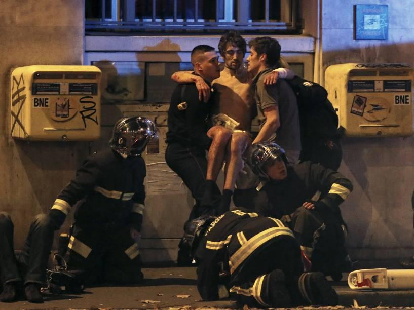 Bombeiros ajudam um homem ferido nos arredores da sala de concertos Bataclan na sequência de um tiroteio em Paris, França - 13/11/2015