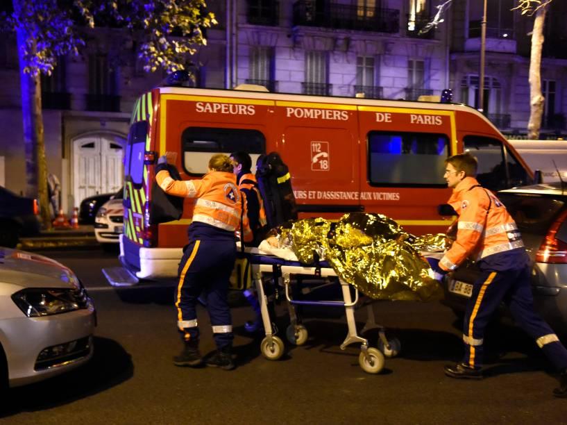 Equipes de resgate carregam uma pessoa ferida no Boulevard des Filles du Calvaire, perto da sala de concertos Bataclan no centro de Paris - 13/11/2015