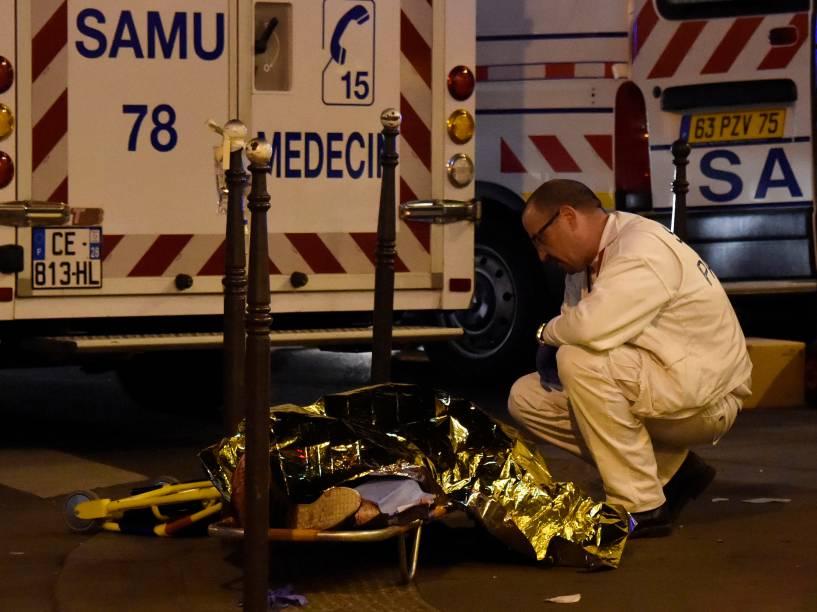 Socorrista fala com uma pessoa ferida em uma maca, perto da sala de concertos Bataclan no centro de Paris - 13/11/2015