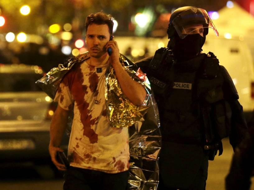 Policial auxilia uma vítima coberta de sangue perto da sala de concertos Bataclan após os ataques em Paris - 13/11/2015
