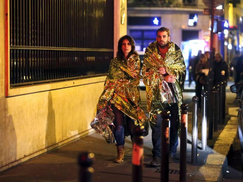 Pessoas se aquecem com cobertores térmicos enquanto andam em uma rua próxima à sala de concertos Bataclan na sequência dos ataques terroristas em Paris - 13/11/2015