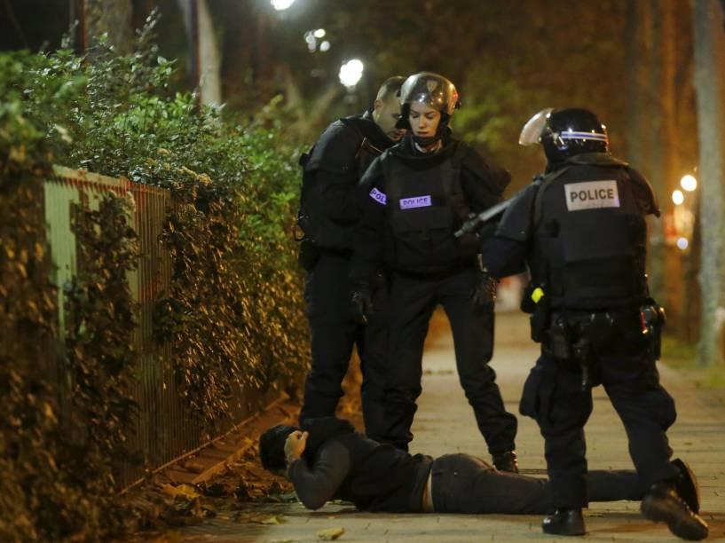 Homem fica no chão enquanto a policiais verificam sua identidade nos arredores da sala de concertos Bataclan na sequência de tiroteios  em Paris, França - 13/11/2015