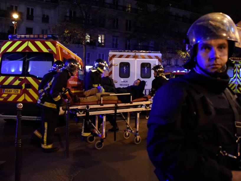Equipe de resgate retira um homem ferido, nos arredores da sala de concertos Bataclan no centro de Paris - 13/11/2015