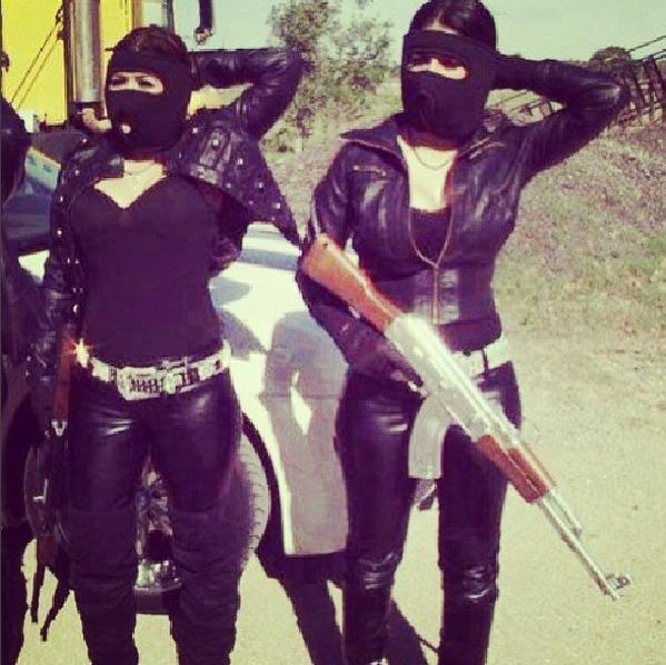 Mulheres se exibem com muito ouro e armas pesadas