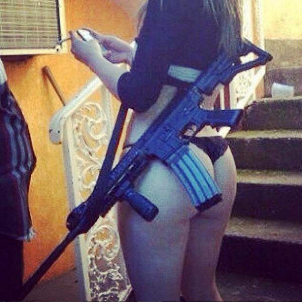 Mulher exibe seu corpo e um fuzil automático