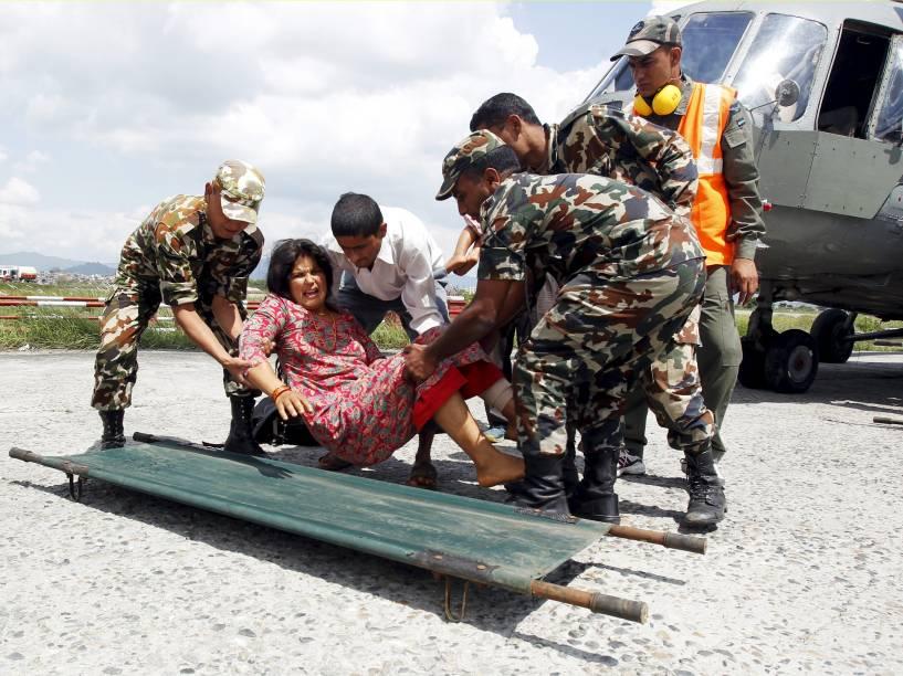 Soldados do exército levam mulher ferida durante terremoto para uma base comunitária no aeroporto de Katmandu - 27/04/2015