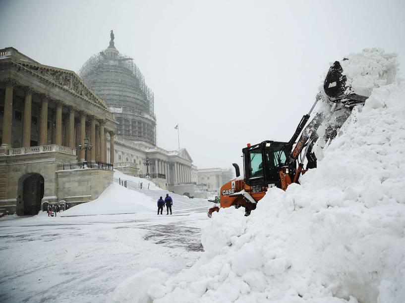 Funcionário usa uma escavadeira para remover neve próximo do Capitólio dos EUA, em Washington