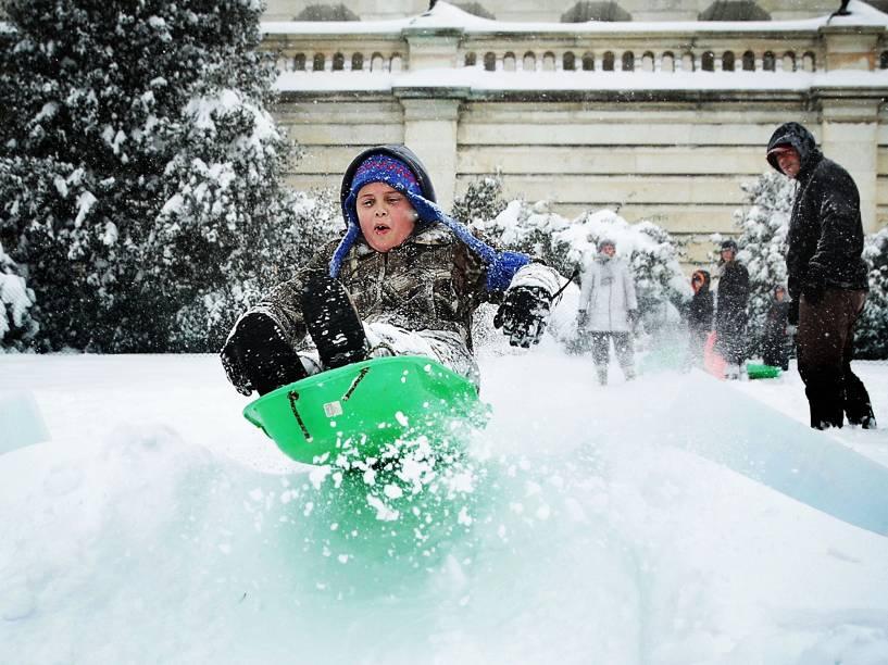 Criança brinca na neve em área perto do Capitólio, em Washington