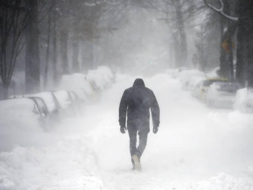 Um homem caminha ao longo de uma rua coberta pela neve durante uma tempestade de inverno em Washington<br>