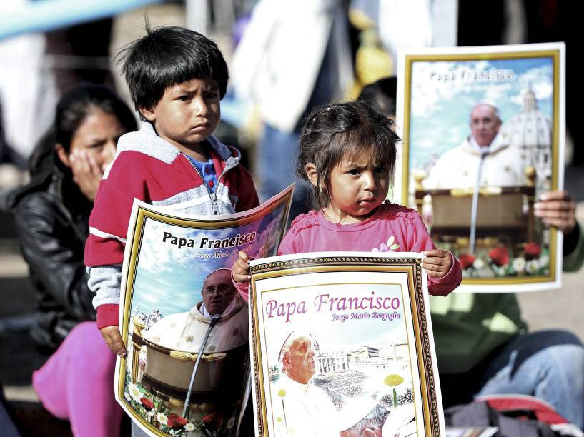 Crianças carregam cartazes com imagem do papa Francisco durante sua chegada ao Santuário El Quinche, no Equador