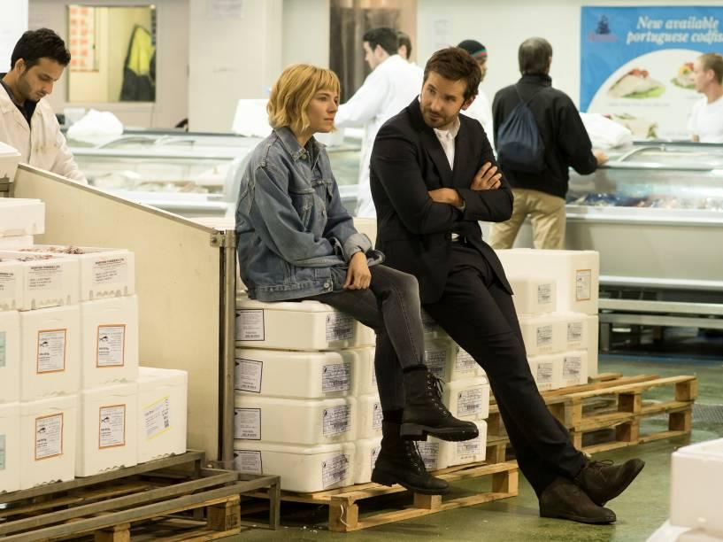 Sienna Miller ao lado de Bradley Cooper em cena do filme Pegando Fogo