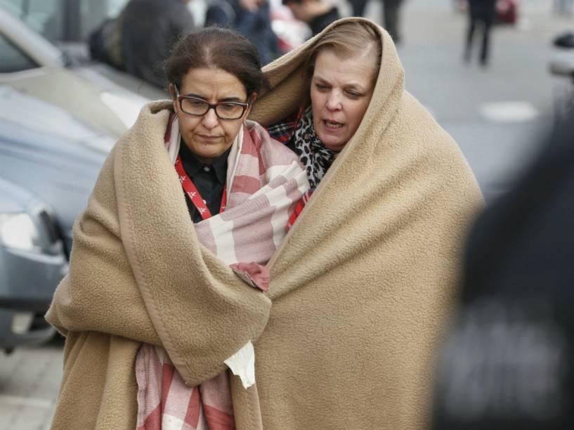 Duas mulheres deixam o Aeroporto de Bruxelas após as explosões