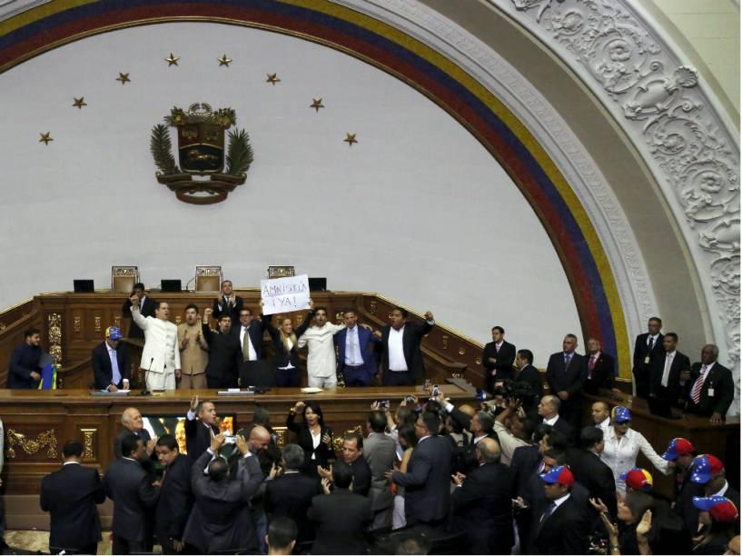 Lillian Tintori, mulher do líder opositor preso Leopoldo López, segura cartaz pedindo anistia ao lado dos novos deputados eleitos