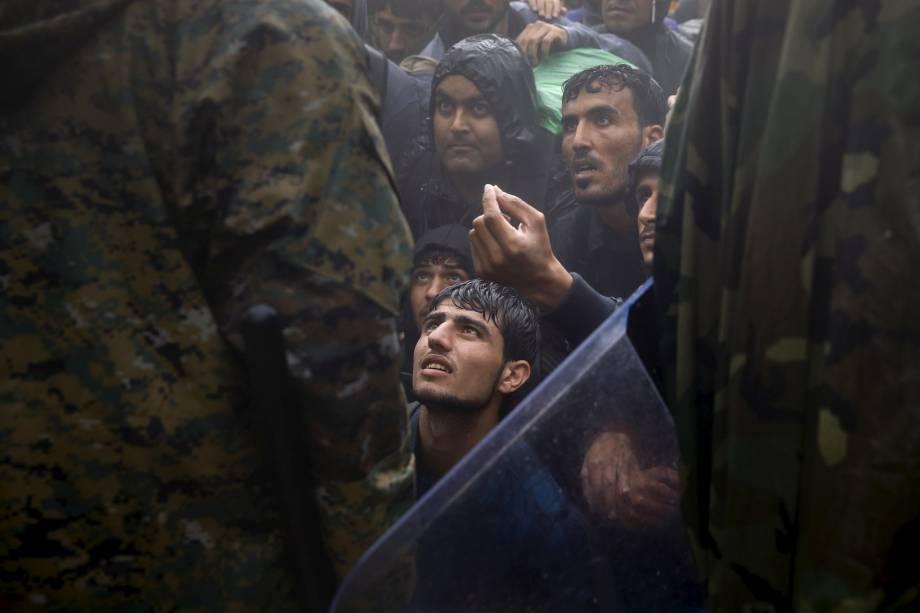 Imigrantes e refugiados imploram para policiais macedônios, para permitir a travessia entre a Grécia e a Macedônia, durante uma tempestade. Foto vencedora do prêmio Pulitzer, o maior prêmio do fotojornalismo - 10/09/2015