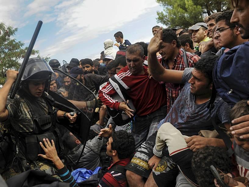 Policial macedônio tenta impedir imigrantes de atravessarem a fronteira entre Grécia e Macedônia. Foto vencedora do prêmio Pulitzer, o maior do fotojornalismo mundial - 22/08/2015
