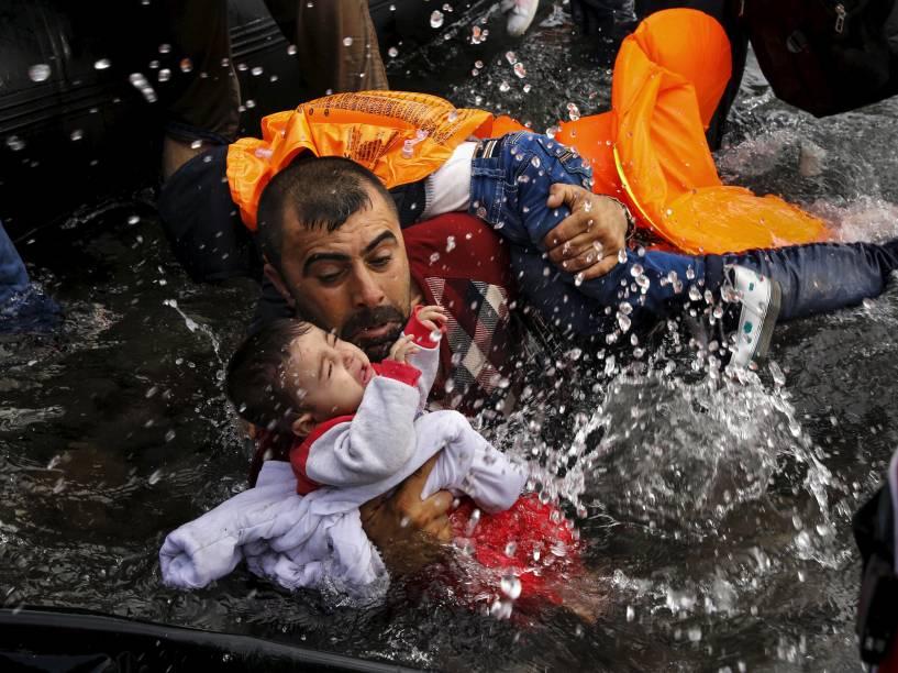 Refugiado sírio segura seu filho, durante travessia em um bote, na ilha grega de Lesbos. Foto vencedora do prêmio Pulitzer, o maior do fotojornalismo mundial - 24/09/2015