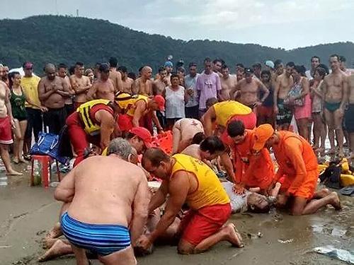 <p>Salva-mar tenta reanimar banhistas após raio atingir a praia do Canto do Forte, em Praia Grande (SP)</p>