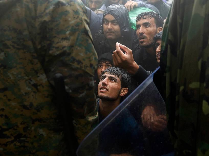Refugiados sírios pedem a policial que libere passagem na fronteira da Macedônia, nesta quinta-feira (10)