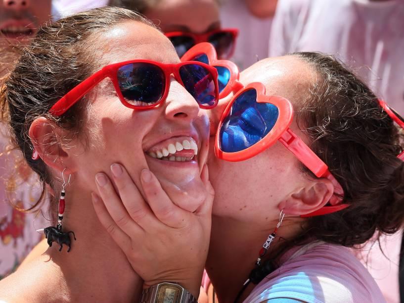 Mulheres se beijam durante as comemorações do Chupinazo, que marcam o começo do Festival de São Firmino, em frente à prefeitura de Pamplona, Espanha