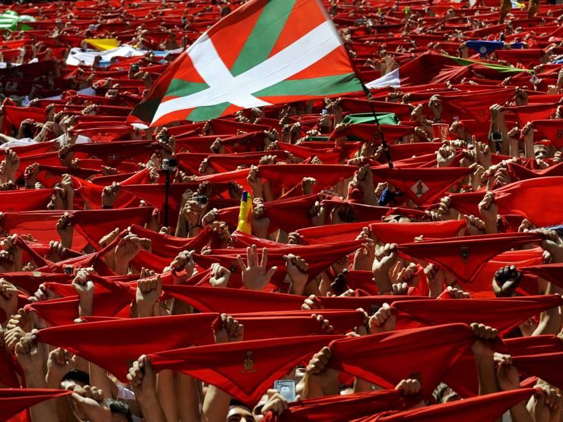 """Bandeira conhecida como """"Ikurrina"""" vista entre os tradicionais lenços vermelhos erguidos por foliões durante o Festival de São Firmino, em Pamplona, Espanha"""