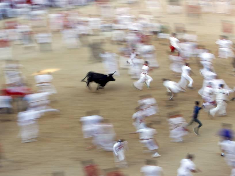 Touro corre atrás da multidão durante a terceira corrida dos touros no Festival de São Firmino, em Pamplona, Espanha. Seis corredores foram hospitalizados após a corrida que durou apenas dois minutos e vinte e sete segundos