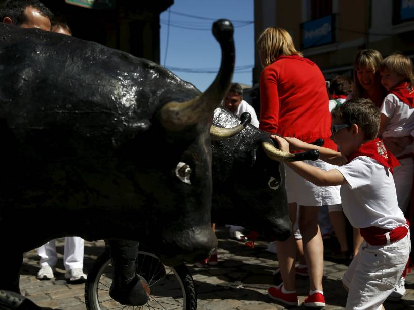 """Garoto para um touro de brinquedo durante o """"Encierro Txiki"""", a """"pequena corrida de touros"""", no Festival de São Firmino, em Pamplona, Espanha"""