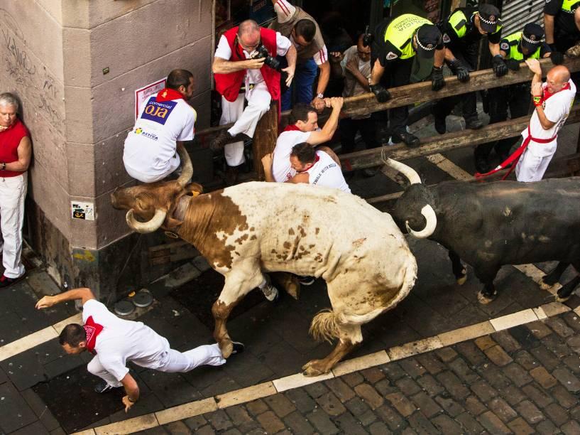 Foliões correm pelas ruas durante a corrida dos touros, parte das celebrações do Festival de São Firmino, em Pamplona, Espanha<br>