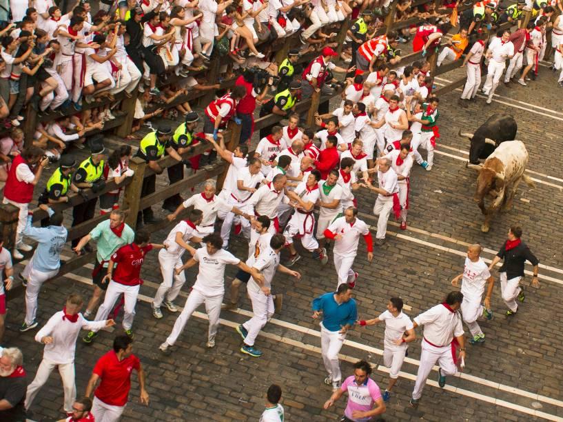 Foliões correm pelas ruas durante a corrida dos touros, parte das celebrações do Festival de São Firmino, em Pamplona, Espanha