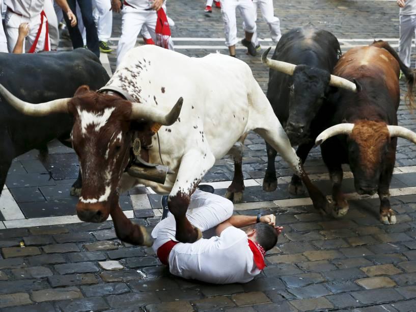 Touro pula sobre um corredor caído durante a a corrida dos touros, parte das celebrações do Festival de São Firmino, em Pamplona, Espanha